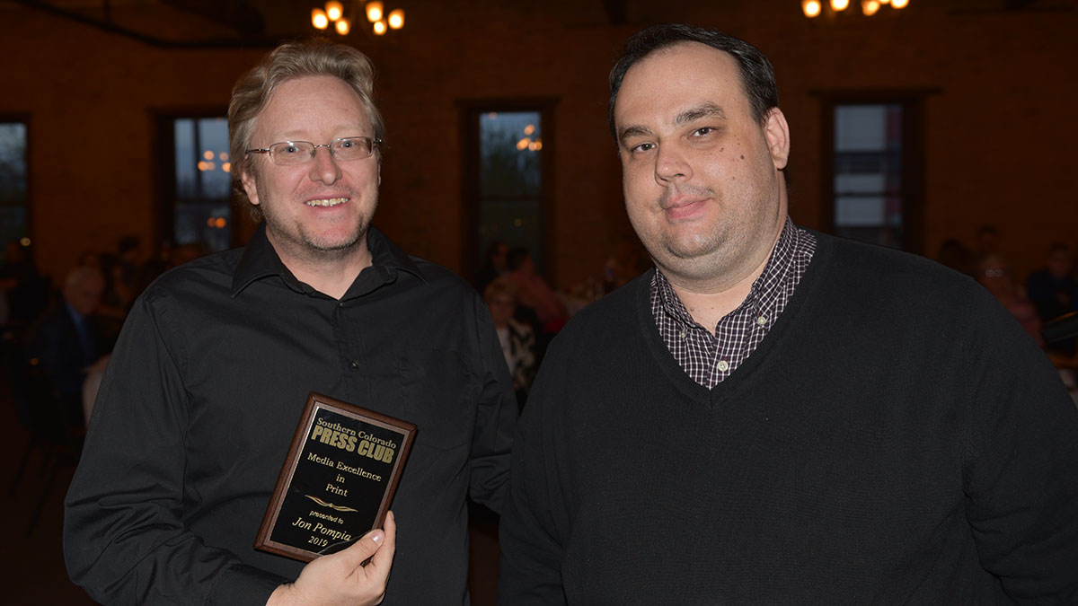 Anthony Sandstrom, left, accepts the Media Excellence Award in print for Jon Pompia of The Pueblo Chieftain from Southern Colorado Press Club Past President Jayson Peters