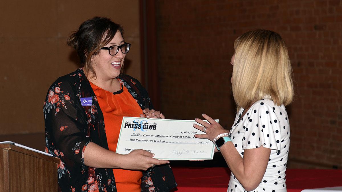 SCPC board member Alyssa Parga presents the Press Club grant to Fountain International Magnet School